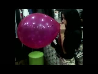 Blowing to pop very large balloon in a clothing store