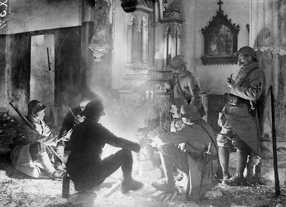 Французские солдаты болтают у костра в поврежденной церкви, Франция, 1916 год.